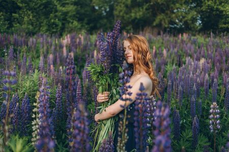 atmosphere: Red-haired women in blue dress with lupines