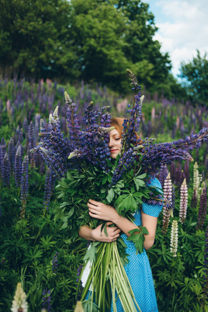 Red-haired women in blue dress with lupines