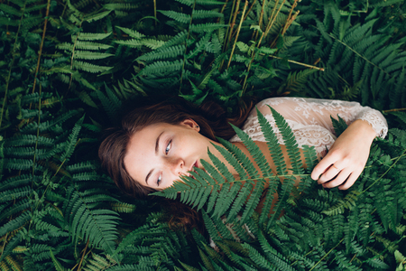 women with red hair in an armful of ferns Stock Photo