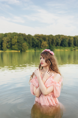 girl in a dress in the water at dawn Stock Photo