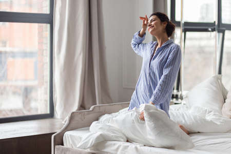 Smiling woman in nightwear holding pillow in hands and looking at window.