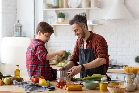 Happy father and adorable son prepare water for cooking pasta. Smiling dad holding pan. Kid sitting on table. Ingredients for making dinner on table. Home kitchen interior. Parenthood and childhood Banco de Imagens