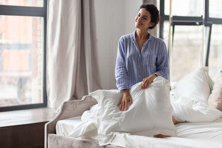 Sensitively smiling young woman in nightwear covering legs with white pillow kneeling in bed. Home bedroom or hotel room with window and mirror. Female portrait after wake up. Good morning