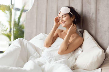 Beautiful female wearing sleep mask rejoicing enjoying new day start. Young woman basking in bed during early morning. Cozy bedroom with soft bed with white duvet and pillows.