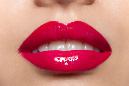 Female plump lips with red glossy lipstick closeup macro shot. Glamor fashion sensual makeup. Magenta women mouth with white teeth. Beauty, visage and cosmetics. Self-care and cosmetology