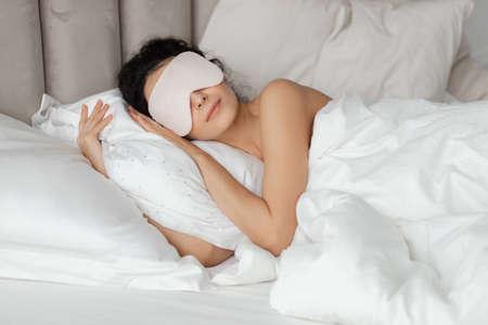 Beautiful woman sleeping seeing dreams wearing sleep mask in comfortable bed lying on soft white pillow orthopedic mattress under duvet blanket on white sheets in bedroom. Good night Standard-Bild