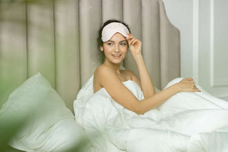 Cheerful brunette woman waking up in soft bed and sitting under blanket duvet without underwear looking aside with gladness and smiling.