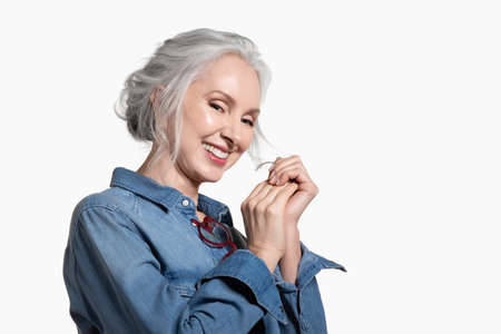 Laughing stylish, pretty senior woman. Elegant charming mid adult lady with gray hair wearing jeans shirt standing in half smiling widely. Fashion and style