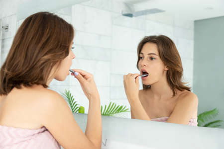 Woman looking in mirror and carefully brushing teeth.