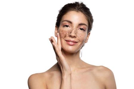 Beautiful girl applying coffee scrub, natural peeling mask on face skin. Stockfoto