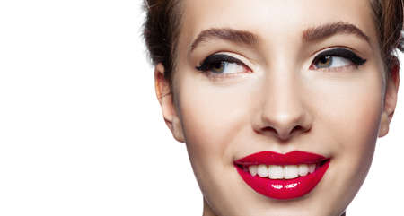 Closeup flirty smiling woman looking aside. Young female face with makeup. Black eyeliner arrows on eyelids and red glossy lipstick on lips. Permanent make-up, cosmetology and visage. Studio shot
