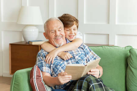 Happy elderly grandfather sitting on couch with adorable kid boy, reading fairy tales together. Involved grandson embracing grandpa looking in book with stories, enjoying relaxing time at home. Banco de Imagens
