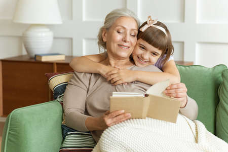 Smiling granddaughter embracing grandmother telling funny fairy tale story sitting on sofa.