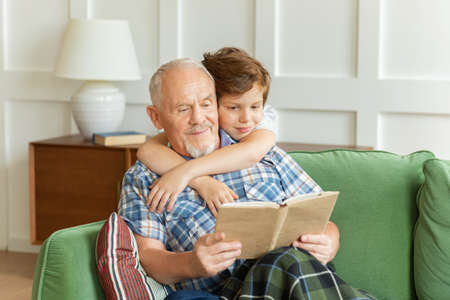 Smart little boy embracing senior man grandpa sitting on couch reading template book at home. Grandson learning with grandfather at home enjoying fairytale spending leisure time together.