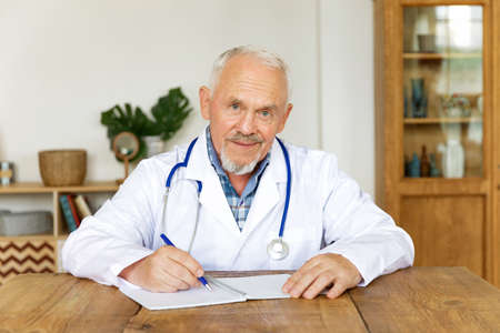 Smiling old male doctor in white uniform at desk fill patient form with medical history or writes patient prescription. Mature senior man GP physician makes notes in journal of client anamnesis.