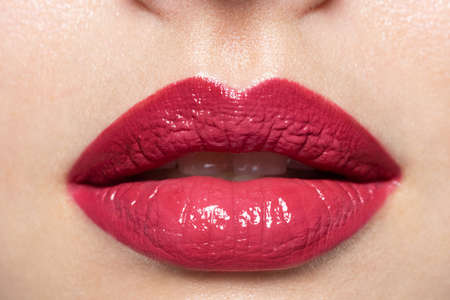 Close up of woman's red lips with bright fashion glossy makeup. Macro photography of beautiful female mouth. Trendy lipstick or lipgloss