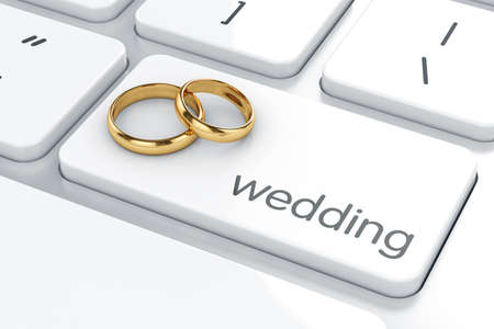 Golden rings on the computer keyboard. Wedding concept
