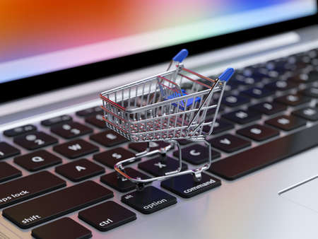 shop online: Illustration of internet shopping and online purchases concept, soft focus view of empty supermarket shopping cart on computer laptop keyboard background