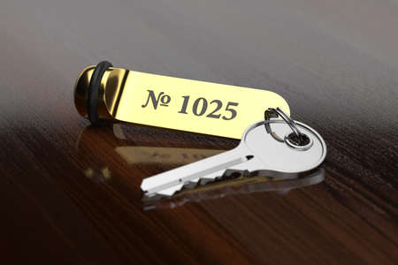 rende: 3d rende of hotel room key with golden lable room number on the wooden table