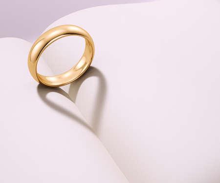 Wedding ring gettando un'ombra a forma di cuore su un libro bianco Archivio Fotografico