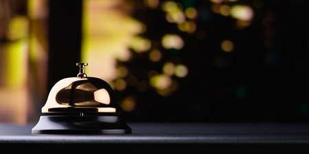 Złoty recepcyjny dzwon na czerń stole z płytką głębią śródpolny czarny tło. Koncepcja usługi
