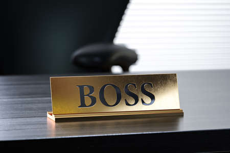 Golden nameplate with Boss text on the wooden table in the office working place, with soft focus depth of field. 3d rendering illustration
