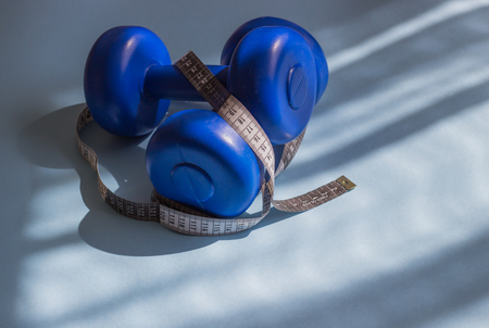 Blue dumbbells, tape measure on a blue background in the sun. Healthy lifestyle, the concept of losing body weight. Cares about the body. Empty place for text. 写真素材