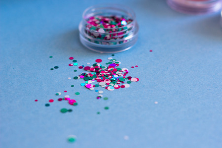 Jar of glitter for nail design, scattered on a blue background.