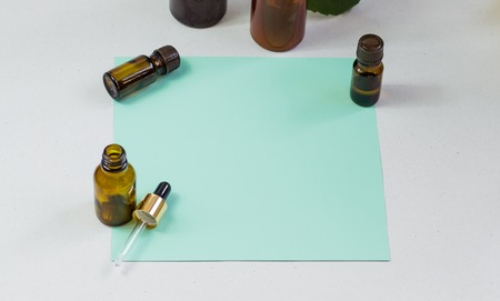 Dark cosmetic bottles and green natural leaves on a light background. Green empty card, sheet for writing. Layoutfor adding inscriptions. The concept of natural environmentally friendly cosmetics