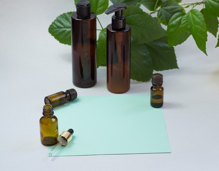 Dark cosmetic bottles and green natural leaves on a light background. Green empty card, sheet for writing. Layoutfor adding inscriptions. The concept of natural environmentally friendly cosmetics Stok Fotoğraf - 122096643