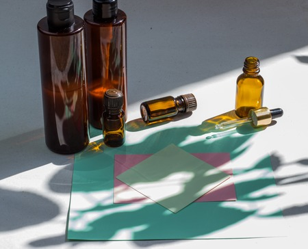 Dark cosmetic bottles and green natural leaves on a light background. Green empty card, sheet for writing. Layout for adding inscriptions. Natural hard light, deep shadows. The concept of natural environmentally friendly cosmetics Imagens