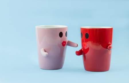 Two cups of coffee on a blue background with a smile facing the mug, hugging each other. The concept of love and relationships. Creative colorful greeting card