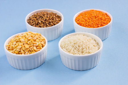 Assorted different cereals on a blue background. Buckwheat, lentils, rice, peas in plates on top, copy of the place. Healthy eating concept