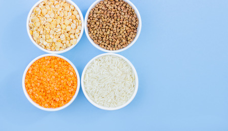 Assorted different cereals on a blue background. Buckwheat, lentils, rice, peas in plates top view, copy space Stockfoto