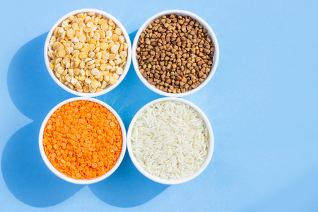Assorted different cereals on a blue background. Buckwheat, lentils, rice, peas in plates top view, copy space 스톡 콘텐츠