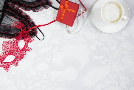 Workplace with red and black lace, lace mask, gift box with a pearl necklace and a cup of coffee on a marble table. Top view, flat lay, copy space