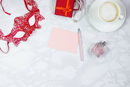 Womens accessories on a white marble table. A pink sheet of paper, a pink pen, a perfume, a gift box, pearls, a glass of coffee and a circling red mask. Layout for adding tags. Top view, flat lay, copy space.