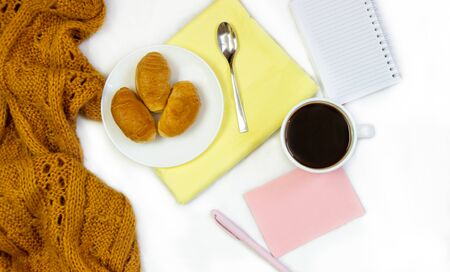 Breakfast in bed. Flat composition with coffee, croissants and a notebook for writing. Lifestyle concept frame. Top view on sheets Фото со стока - 130998149