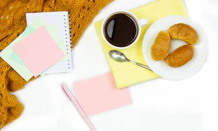 Breakfast in bed. Flat composition with coffee, croissants and a notebook for writing. Lifestyle concept frame. Top view on sheets Фото со стока - 130998152