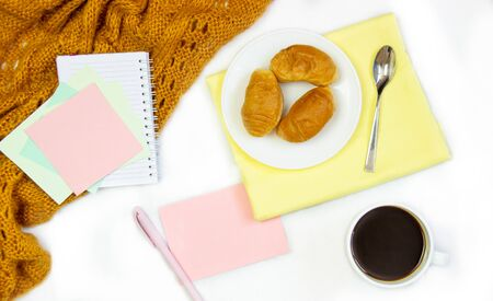 Breakfast in bed. Flat composition with coffee, croissants and a notebook for writing. Lifestyle concept frame. Top view on sheets Фото со стока - 130998153