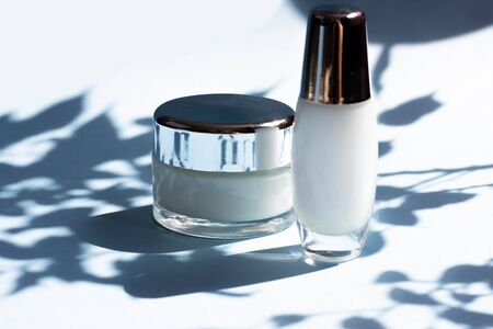 Face cosmetics. Jars of cream, face mask on a blue background with hard shadows from the leaves. Beauty blogger, procedures salon concept. Minimalism