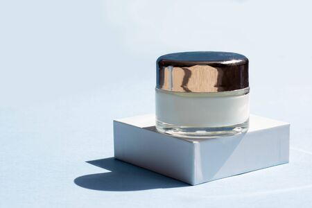 Cosmetic products for the face. Jar of cream, face mask on a white box. Beauty blogger, procedures salon concept. Minimalism