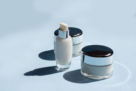 Face cosmetics. Jars of cream, serum and face mask on a blue background with hard shadows. Beauty blogger, procedures salon concept. Minimalism Фото со стока