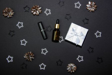 Beautiful composition on a black background with a white gift box, cosmetics and decorations. View from above. Copy space