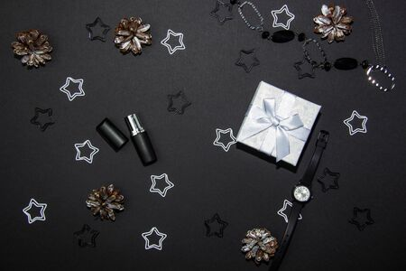 Beautiful composition on a black background with a white gift box, cosmetics and decorations. View from above. Copy space Фото со стока - 131364506