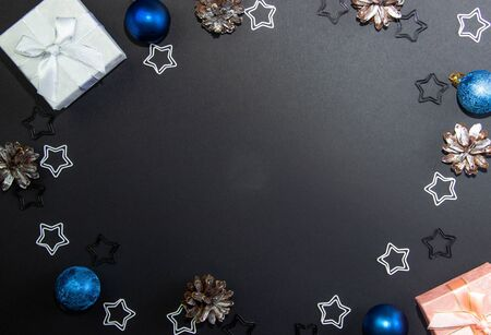 Beautiful Christmas layout for writing on a black background with Christmas gift boxes and Christmas decorations. View from above. Copy space Фото со стока