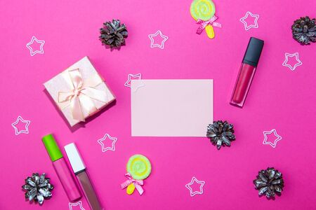 Christmas decorations on a bright pink background. Blank sheet for writing, gift box, christmas cones and stars on christmas background. Layout for recording