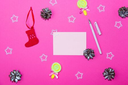 Christmas decorations on a bright pink background. Blank sheet for writing, gift box, christmas cones and stars on christmas background. Layout for recording. Фото со стока