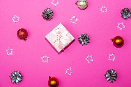 New Year decorations on a bright pink background. Gift box, Christmas cones and stars on a Christmas background Фото со стока
