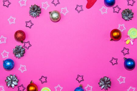 Christmas decorations on a bright pink background. Christmas balls, christmas cones and stars on christmas background. Layout for recording.